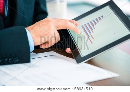 Business - banker, Manager or expert evaluates the figures on tablet computer and compares the development of the business in real time to quickly and efficient advise and act as consultant