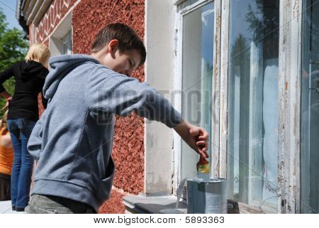 Boy Staining Window On The Outside.