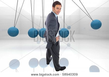 Cheerful businessman standing with hands on hips against blue newtons cradle