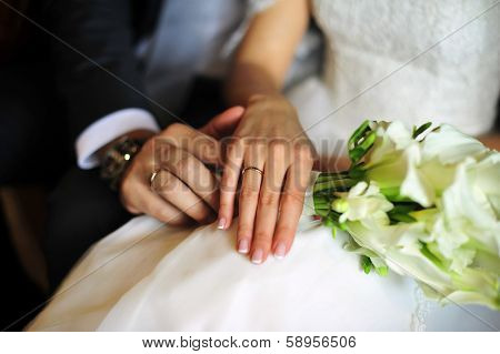 Bride and groom's hands with wedding rings