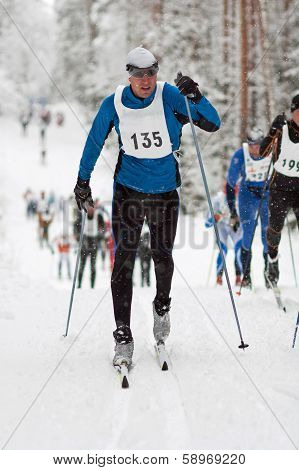 Sportsman In Classic Style Cross Country Skiing Race, Competitors Following