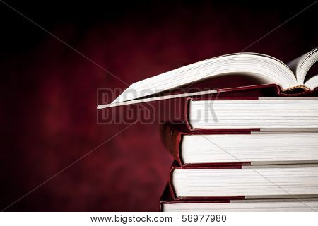 Stack of old books, with one open, over red grunge background.