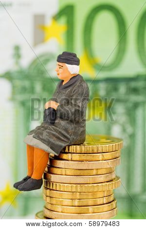 pensioner sitting on money stack, symbol photo for pension, retirement, old-age security