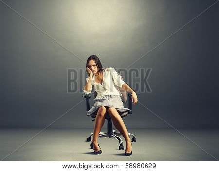 sorrowful businesswoman sitting on the chair in empty dark room