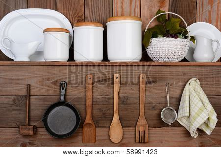 Closeup of a rustic kitchen wall. One shelf with canisters, plates and a basket. Hanging on the wall below are wooden utensils, frying pan and towel.