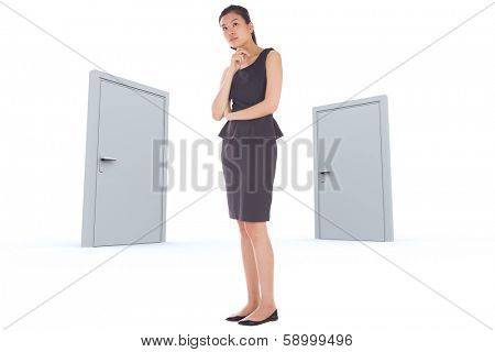 Thoughtful businesswoman against closed doors
