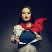 Young pretty woman opening her shirt like a superhero. Super girl, image toned. Beauty saves the world. poster