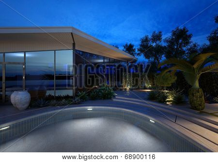 Upmarket modern design house with a glass facade and illuminated swimming pool at night with plants on the paved surround lit by electric spotlights