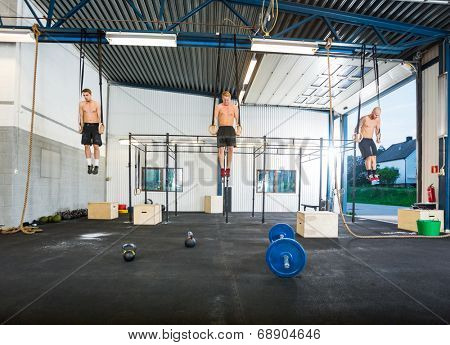 Full length of young male athletes exercising on gymnastic rings at gym