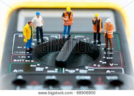 Team Of Miniature Workers On Top Of Multimeter. Macro Photo