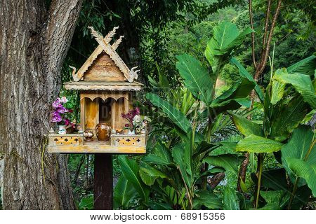 Spirit House In Thailand With Flowers In Vases And Some Wreathes.