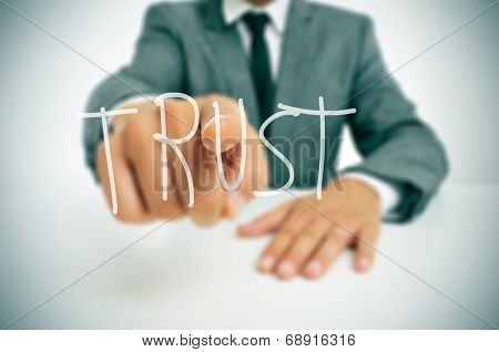 businessman sitting in a desk pointing the word trust written in the foreground