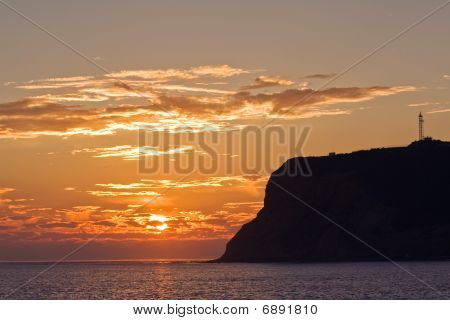 Point Loma silhouetted behind a setting sun and orange sky on the coast of California where San Diego Bay meets the Pacific Ocean poster