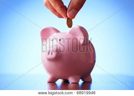Man Placing A Coin Into A Piggy Bank