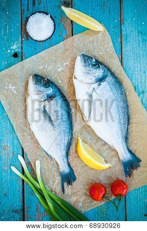 Two Raw Dorada Fishes With Lemon, Green Onions And Cherry Tomatoes