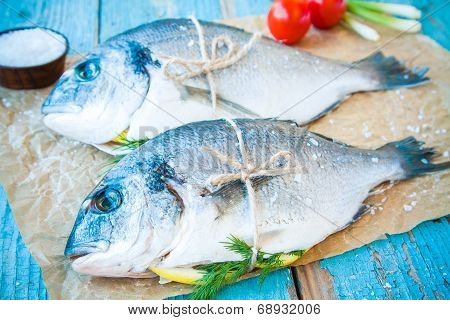Two Raw Dorada Fishes With Lemon, Green Onions, Cherry Tomatoes And Sea Salt