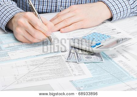 Male Filling Out 1040 Usa Tax Form - Studio Shot