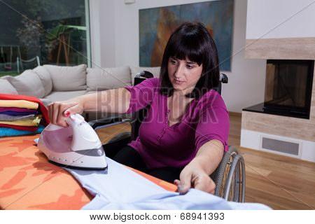 Woman On Wheelchair During Ironing