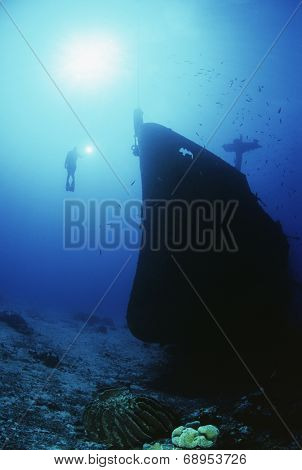Underwater shoot of female scuba diver exploring sunken ship