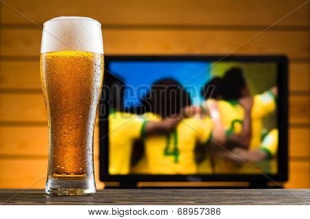 A Glass Of Cold Beer On The Table, Football Match In Background