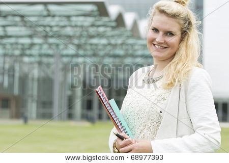 Young Student Smiling With Her Schoolbooks In Her Hands