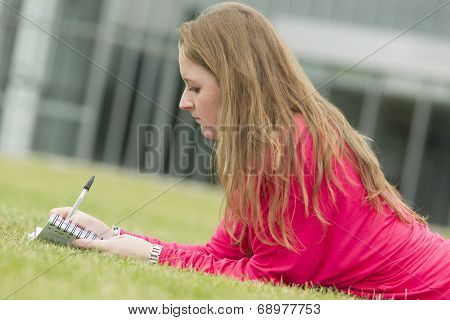 Student Lies In The Grass And She Write Something