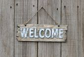 Weathered wood welcome sign hanging on wooden background poster