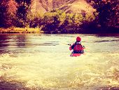 a woman kayaking on a rough river during fall toned with a retro vintage instagram filter  poster