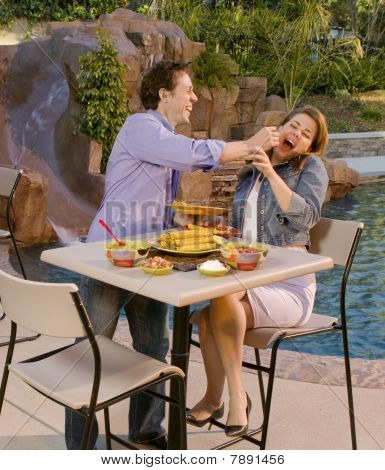 Couple Eating At Poolside, Man Giving Woman Tortilla Chip