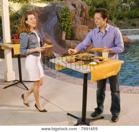 Couple Getting Food At Poolside