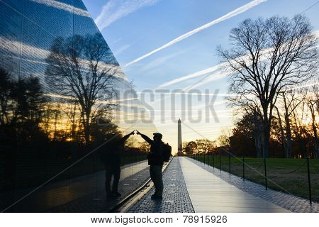 Washington DC - A Veteran looks for a name at Vietnam Veterans Memorial Wall  at sunrise poster