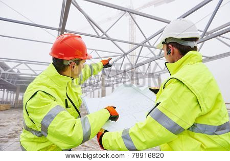 male engineers construction foreman managers outdoors indoors at building site with blueprints