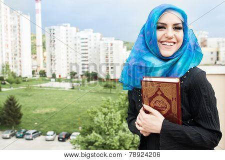 beautiful muslim woman wearing hijab and holding holy book Koran