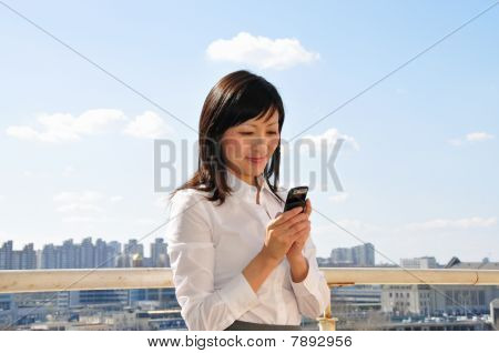 Businesswoman with mobile phone outside