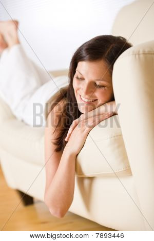 Smiling Woman Lying Down On Sofa