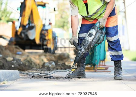 Builder worker with pneumatic hammer drill equipment breaking asphalt at road construction site poster