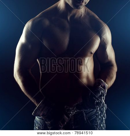 Sexy macho man with chain and gloves in dark poster