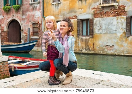 Baby Girl And Mother Poiting On Copy Space While In Venice, Italy