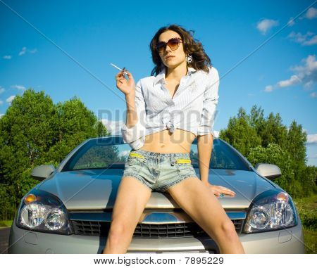 Woman Is Smoking On A Car Hood