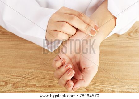 Taking heart rate oneself by hand, on wooden table background