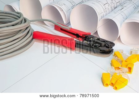 Drawing rolls, cat 5 cable, crimping pliers, connectors and boot caps composition