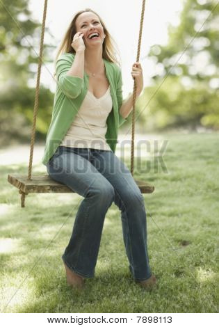 Woman Using Cellphone on a Swing