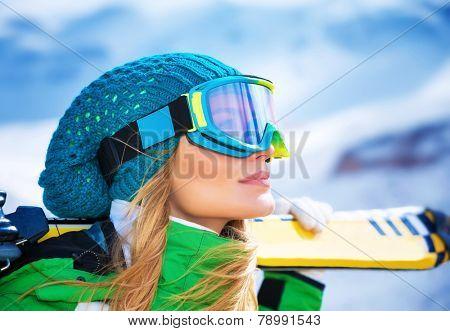 Closeup portrait of beautiful skier girl wearing mask and holding ski, enjoying winter holidays