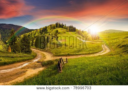 Cross Road On Hillside Meadow In Mountain At Sunset