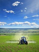 Farming Tractor Plowing And Spraying On Field, vertical. poster