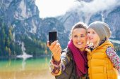 Happy mother and baby making selfie on lake braies in south tyrol italy poster