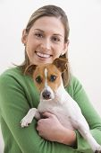 A attractive young woman is wearing a green sweater and smiling while holding a dog. Vertical shot. poster