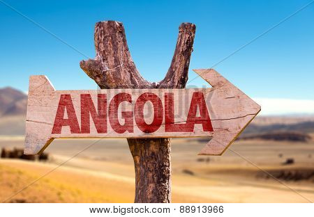 Angola wooden sign with desertic road background