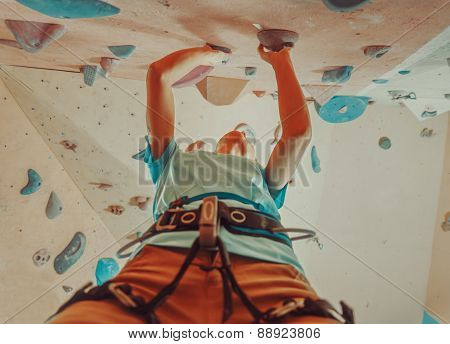 Girl In Safety Harness Climbing In Gym