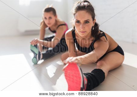 Group of fit women working stretching leg muscles back to warm up at gym fitness, sport, training an